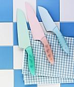 Various knives on a tea towel