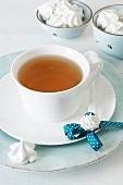 Eine Tasse Tee mit Teelöffel und Sahnetupfen-Magneten