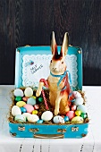 A papier-mâché rabbit with Easter eggs and chocolate eggs in a child suitcase
