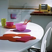 Coloured glass bowls and felt coasters on a white table