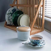 A cup of coffee and a sugar pot in front of a plate drainer