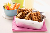 Spicy waffles and vegetable crudités in a lunchbox