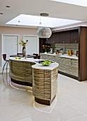 Designer Küche mit geschwungenem Küchenblock vor Einbauküche und abgehängter Decke mit offenem Ausschnitt