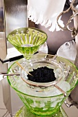 Black caviar in glass bowls on ice
