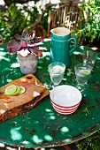 A garden table set with lemonade, a chopping board and a potted plant