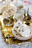 Crockery and a bunch of flowers on a golden tray