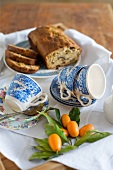 Kumquats, blue and white cups and fruit cake
