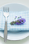 A fork, a napkin and a lavender flower on a plate