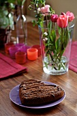 A heart-shaped chocolate cake with flowers and candles in the background