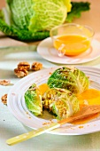 Savoy cabbage parcels filled with walnuts and rice with pumpkin sauce