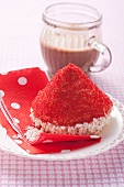 A cake topped with a red hat made of desiccated coconut and sugar sprinkles