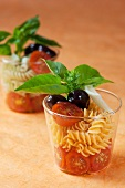Pasta salad with cocktail tomatoes, olives and basil