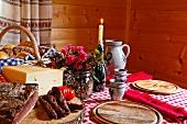 Marende (Brotzeit, Südtirol) in Bauernstube mit Speck, Wurst, Käse, Brot und Wein