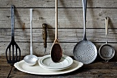 Old kitchen utensils and crockery against a wooden wall