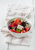 A portion of Greek salad made with feta cheese, cucumber, pepper, tomato and olives