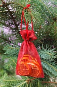 Dried orange slices in an organza sack hung on a Christmas tree