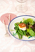 A fried scallop with green beans and baby spinach