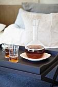 Gläser und Karaffe mit Getränk auf Frühstückstablett im Bett