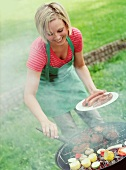 A woman barbecuing in a garden