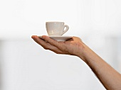 A hand holding an espresso cup