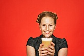 A smiling woman holding a glass of coffee
