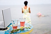 A laptop and a glass of juice on a table by the sea