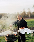 A man barbecuing sausages