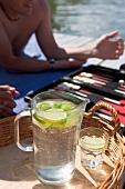 Junge Leute am Bootssteg mit Backgammon-Spiel und Limonade