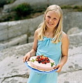 A blonde girl serving a berry tart in the open air