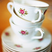 A stack of coffee cups with a rose pattern
