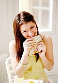 A smiling woman eating from a napkin