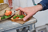 A hand taking a slice of bread topped with tomatoes and basil