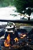 A teapot on a camp fire