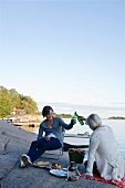 Two women having a picnic by the sea in Stockholm (Sweden)