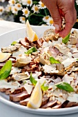 Chicken salad being sprinkled with pine nuts