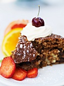 A slice of chocolate cake with fruit and cream