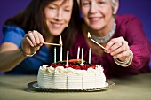 Two women lighting candles on a birthday cake