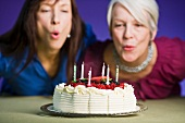 Two women blowing out candles on a birthday cake