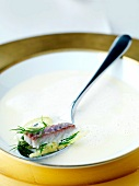 Fish soup with pieces of fish on a spoon