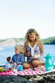 Mutter und Sohn beim Picknick am See
