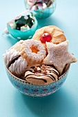 Various Christmas biscuits in a floral bowl
