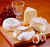 Various cheeses on wooden board, figs and grapes
