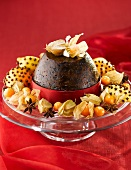 Christmas pudding with cape gooseberries on red cloth
