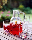 Cranberry juice in glass jug and glasses on garden table