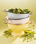 Pea pods in stacked colanders