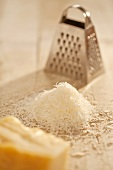 Pile of Freshly Grated Parmesan Cheese with Cheese Grater; Wedge of Parmesan Cheese