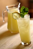 Glass of Lemonade with Lemon and Mint Garnish; Pitcher of Lemonade