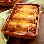 Baked Chicken Enchiladas with Melted Yellow and White Cheese; In Baking Dish