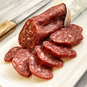 Salchichon De Vic; Catalonian Style Dry Salami; Sliced on Cutting Board