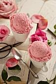 Roseneis in Tassen, Blütenblätter, Löffel, Buch und Schere
